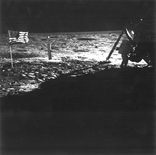 The American flag shown in the first manned lunar landing mission, Apollo 11 on July 20, 1969. Astronaut Neil Armstrong is visible to the right, removing science equipment from a storage bay of the lunar module. The brilliant sunlight emphasizes the U. S. Flag to the left. The object near the flag is the Solar Wind Composition Experiment deployed by astronaut Buzz Aldrin earlier.