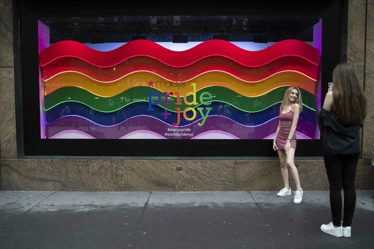 In this Wednesday, June 19, 2019, photo, a visitor to Herald Square takes a photo with the Pride and Joy window display at the Macy's flagship store in New York. For Pride month, retailers across the country are selling goods and services celebrating LGBTQ culture. Macy's flagship store is adorned with rainbow-colored Pride tribute windows, set in the same space as its famous Christmas displays. (AP Photo/Mary Altaffer)