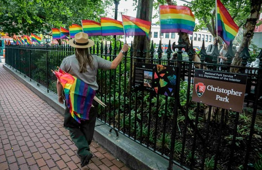 A National Park Service ranger place rainbow flags, representing LBGTQ pride, along fencing around Christopher Park, Friday June 14, 2019, in New York's Greenwich Village. June is Pride Month, celebrated each year to mark the 1969 Stonewall rebellion, a series of violent confrontations between the gay community and police, that occurred near the park at a gay bar called the Stonewall Inn. (AP Photo/Bebeto Matthews)