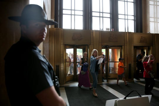 An Oregon State Police Officer stands guard as protesters enter the Oregon State Capitol for the Oregon Senate floor session at the Oregon State Capitol in Salem on June 23, 2019. People rallied in support of Republican senators who walked out of the Capitol over HB 2020, a greenhouse gas emissions cap-and-trade bill. The Oregon Senate was not able to reach quorum on Sunday.
