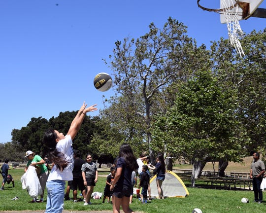A young girl shoots a basketball at the Gil Basketball Academy 10th anniversary barbecue. June 22, 2019.