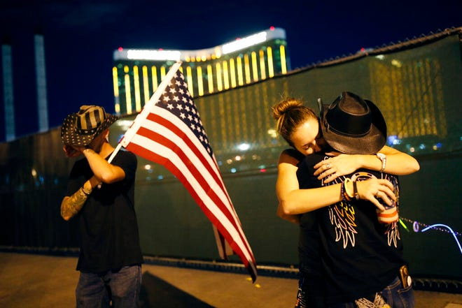 FILE - In this Oct. 1, 2018, file photo, Megan Murphy, right in hat, embraces Cara Knoedler as Kenneth Wright wipes his eyes on the first anniversary of the mass shooting in Las Vegas.  Casino giant MGM Resorts International says more than 4,000 people are seeking compensation related to the Las Vegas Strip shooting that left 58 people dead, and it's suing its insurance company for legal costs.  A lawsuit filed Wednesday, June 19, 2019  in U.S. District Court in Las Vegas alleges breach-of-contract by Illinois-based Zurich American Insurance Co. (AP Photo/John Locher, File)
