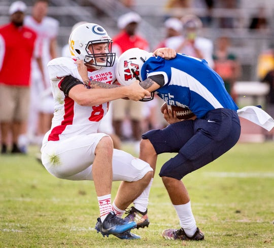 East's' Grant Highstreet (CVC), left, pulls down West quarterback Anthony Cervantes (Western) during the 52nd annual Tulare/Kings Counties All-Star Football Game on Saturday, June 22, 2019.