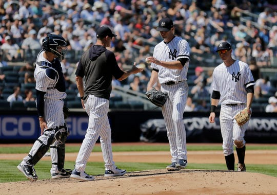 New York Yankees starting pitcher J.A. Happ, second from right, is pulled from a baseball game during the fifth inning against the Houston Astros at Yankee Stadium, Sunday, June 23, 2019, in New York. (AP Photo/Seth Wenig)
