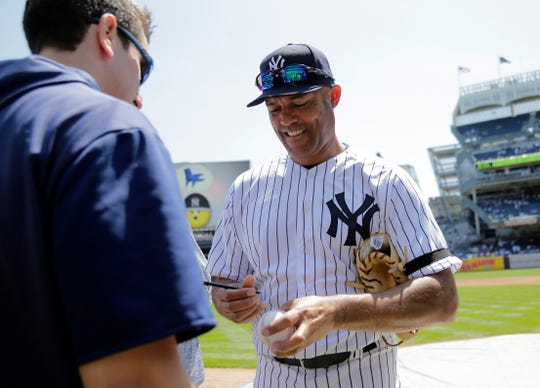 Former New York Yankee Mariano Rivera signs balls for people on the field during Old Timer's Day at Yankee Stadium, Sunday, June 23, 2019, in New York. (AP Photo/Seth Wenig)