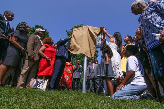 State Sen. Darius Brown, left, and high schooler Savannah Shepherd, right, along with members of the Delaware Legislative Black Caucus and community members unveil a state historic marker of the only documented lynching site in Delaware Sunday, June 23, 2019, at Greenbank Park in Pike's Creek.