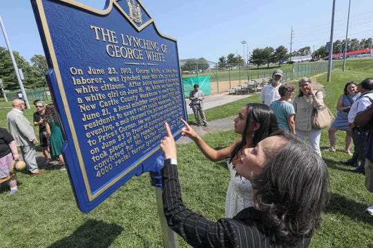 U.S. Representative Lisa Blunt Rochester, left, and local high schooler Savannah Shepherd, right, read a state historic marker of the only documented lynching site in Delaware Sunday, June 23, 2019, at Greenbank Park in Wilmington Delaware.