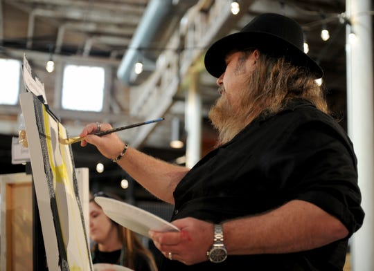 Chris Mayfield paints in the second round of Art Battle Wichita Falls Saturday, June 22, 2019, inside The Warehouse.