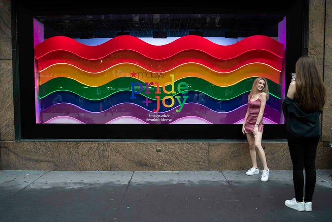 In this Wednesday, June 19, 2019, photo, a visitor to Herald Square takes a photo with the Pride and Joy window display at the Macy's flagship store in New York. For Pride month, retailers across the country are selling goods and services celebrating LGBTQ culture. Macy's flagship store is adorned with rainbow-colored Pride tribute windows, set in the same space as its famous Christmas displays.