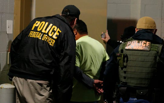 Immigration and Customs Enforcement agents escort a target during a raid in Richmond, Virginia, on Oct. 22, 2018.