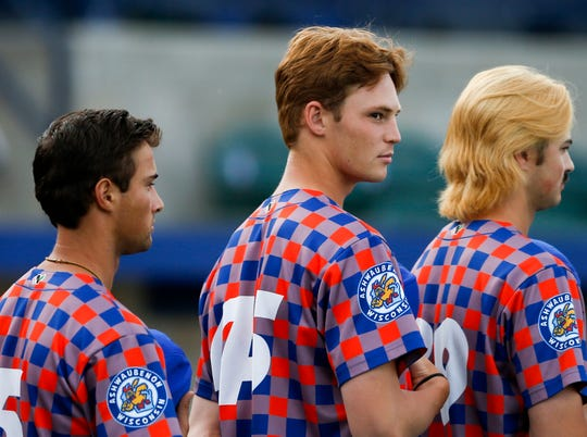 Green Bay Booyah pitcher Jack Mahoney, center, stands during the national anthem before the Northwoods League baseball game between the Fond du Lac Dock Spiders and the Green Bay Booyah on June 19.