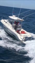 Petty Officer John Gedz, United States Coast Guard, pumps out water on a sport boat that was taking on water 40 miles from Manasquan, N.J. on June 23, 2019.