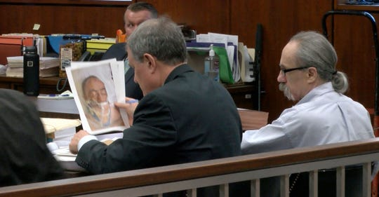 Arthur Haskoor looks at a photo held by his attorney Richard Archer that show his condition after he was medevaced to a hospital after an altercation with his wife outside thir Plumsted Township home in 2015.  He is on trial for her murder before Judge is Guy P. Ryan in State Superior Court in Toms River Monday, Jun 24, 2019.
