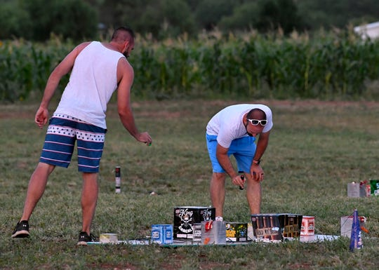 Men check the fireworks before Saturday's Boombah show at the Smith family property.