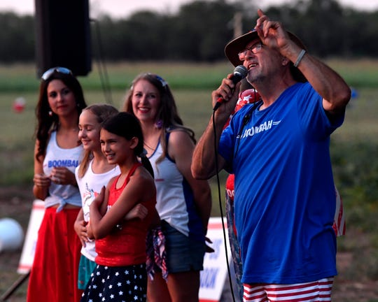 Doug Smith addresses the crowd gathered on his property before Saturday's Boombah fireworks display. Up to 1,700 people were estimated by the family to have shown up for the show, thanks to advertising on social media.