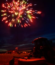 A tractor is lit by exploding fireworks during Saturday's Boombah show off Summerhill Road north of Abilene.