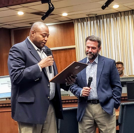 Mayor Anthony Williams reads a plaque for Place 5 Abilene City Council member Kyle McAlister. McAlister won re-election to Place 5 after a close runoff election June 15.