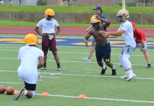 Battle Creek Central running back Jaquan West takes a handoff during a drill at the BCC Champions Camp at C.W. Post Field on Monday.