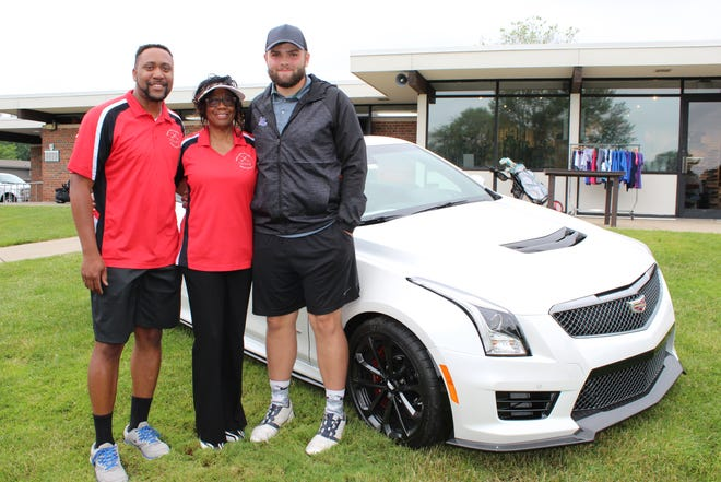 Harper Creek's Jack Kyger stands with Gene Hughes, Jr. and Dorothy Hughes after he hit a hole-in-one to win a $50,000 Cadillac.