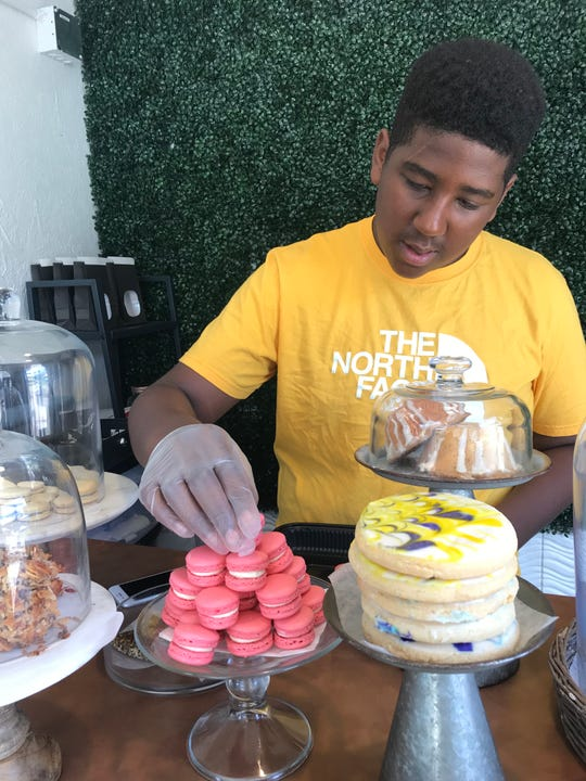 Jordan Edwards places more strawberry macarons out at his bakery, JJ's Sweet Treats, located at the BC Cargo marketplace in downtown Battle Creek.