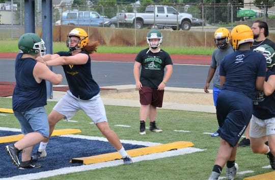 Offensive linemen go through a drill during the Champions Camp at C.W. Post Field on Monday.