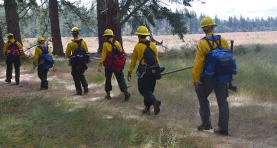 Firefighters receiving training at DNR's Western Washington Interagency Wildfire Training Academy carry packs and tools in late June. Hundreds of the state's 1,000 certified wildland firefighters received training at the academy in June.