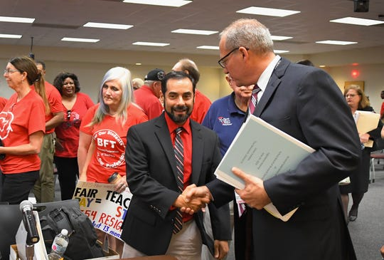 Anthony Colucci, president of the Brevard Federation of Teachers, and Mark Mullins, Brevard Schools superintendent, shake hands following the meeting. Colucci has vowed to fight on for a bigger raise. An estimated 900 teachers and their supporters rallied outside and eventually filled the school board meeting room in Viera on Monday. They were fighting for a better raise than was proposed by superintendent Mark Mullins. After hearing both sides of the issues, the school board members eventually voted 4-1 to back the Mullins plan over the teacher's union plan that an impartial magistrate endorsed.
