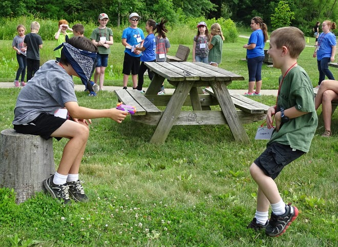 """Lincoln Martin, left, squirts Logan Fruth during a game of """"The Sneaky Mice"""" during the Crawford Park District's Summer Nature Camp at Lowe-Volk Park in Crestline on Monday morning."""