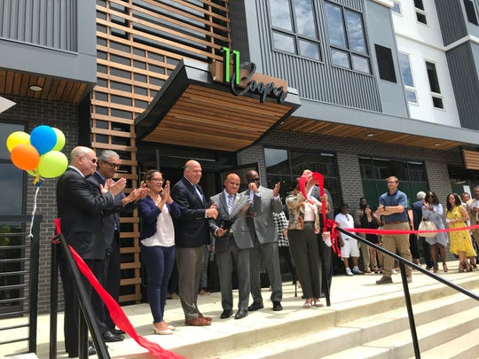 Camden Mayor Frank Moran (center) cuts the ribbon on 11 Cooper, a new apartment complex on the Camden Waterfront.