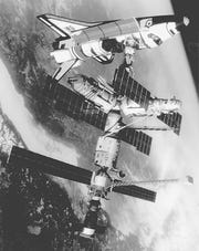 The space shuttle Atlantis, top, and the Russian Mir space station are shown in a docking configuration in this 1993 NASA illustration.