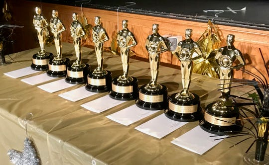 Eight Oscar statues stand in the spotlight of the Linden High School auditorium before being awarded at the Linden Public School Academy Awards, which recognize top student-created videos.