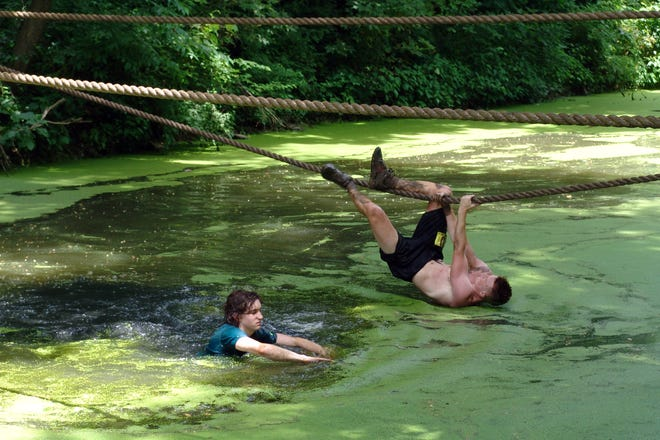 Contestants make their way across a water feature during the Indian Mud Run in Coshocton on Saturday.