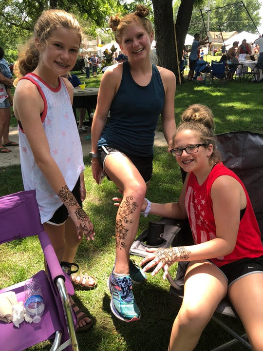 Annika and Sydney Schulz and Riley Gingrich show off their henna tattoos at the 2018 Norwalk 4th of July celebration in City Park.