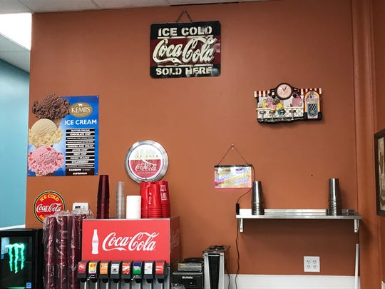 Classic Coca-Cola memorabilia adorns the wall behind the counter at Sugar Shack in Altoona. The restaurant's new location will have several updated features while maintaining the classic diner feel.