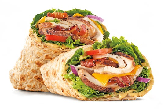 Chicken Club Wrap - Carved slow roasted chicken breast with pepper bacon, cheddar cheese, honey mustard, green leaf lettuce, tomato, and red onion in a whole wheat wrap