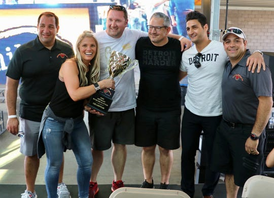 Michele Haskell of Kozy Lounge in Hazel Park holds the trophy for this year's best burger. Behind her (from left) are  Emmet Baratta of Fairway Packing, Rob Haskell of Kozy Lounge, Scott Rutterbush of Dine Drink Detroit, Gino Barratta of Fairway Packing and Joe Barratta of Fairway Packing.