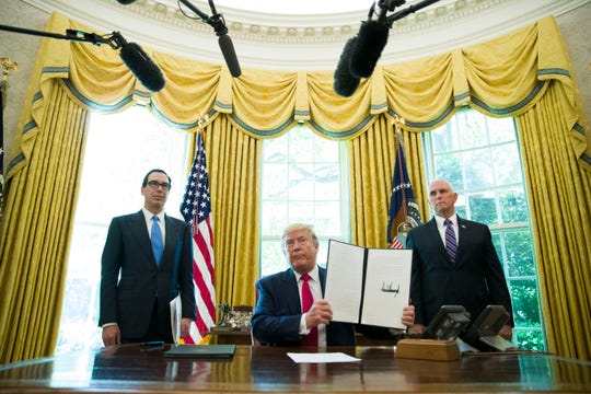 President Donald Trump holds up a signed executive order to increase sanctions on Iran, in the Oval Office of the White House, Monday, June 24, 2019, in Washington.