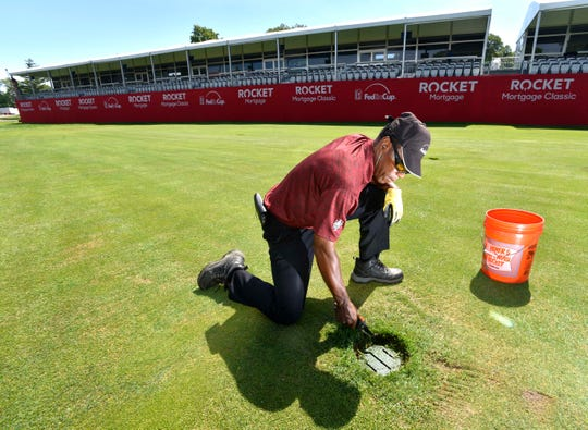 Detroit Golf Club grounds crew member Keenan 'Coach K' Coleman, of Detroit, trims grass around fairway drains and yard markers on the 18th hole.