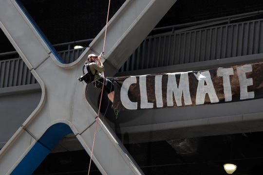 A man rappels down the side of the Port Authority Building with a sign during a climate change rally Saturday, June 22, 2019, in New York. Activists blocked traffic along 8th Avenue during a sit-in to demand coverage of climate change by the New York Times.