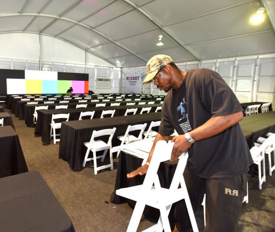 Display Group employee Matthew Campbell, of Detroit, sets up chairs in the media center.