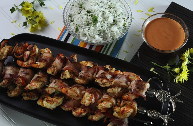Smoked bacon wraps shrimp that has been marinaded in a wine-citrus-garlic mixture. Comeback sauce, a Mississippi staple of mayo, ketchup, hot sauce and flavorings, right, makes a fine companion. (Abel Uribe/Chicago Tribune/TNS)