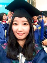 This 2016 selfie provided by her family shows Yingying Zhang in a cap and gown for her graduate degree in environmental engineering from Peking University Shenzhen Graduate School.