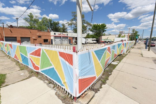 A colorful privacy screen is seen along 7 Mile at Bauman, obscuring a closed business lot in preparation for the Rocket Mortgage Classic golf tournament.