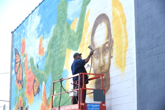 Artist Fel'le works on a mural on 7 Mile near the Chrysler Freeway off-ramp on Friday.