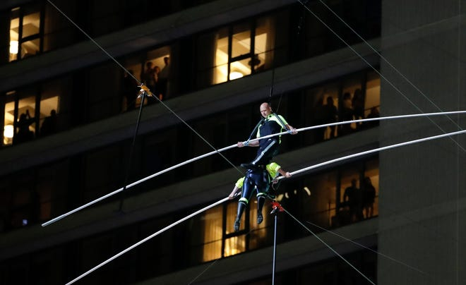 Aerialists Nik Wallenda, top, steps over his sister Lijana as they walk on a high wire above Times Square, Sunday, June 23, 2019, in New York.