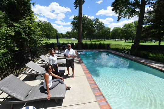 Homeowners Leigh Coleman, left, Doris Ewing and Lane Coleman can watch the action on the 9th hole at the Detroit Golf Club's North Course from the Colemans' pool.