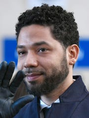 FILE - In this March 26, 2019, file photo, actor Jussie Smollett smiles and waves to supporters before leaving Cook County Court after his charges were dropped in Chicago.