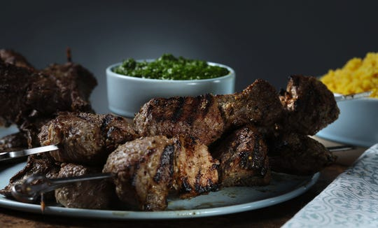 Lamb kebabs, front, get a marinade with lemon, wine, onions, garlic, Dijon and herbs. They go beautifully with the herb condiment called z'hug, seen in back. Steak kebabs, left, marinate in a lime-garlic-herb mixture. (Abel Uribe/Chicago Tribune/TNS)