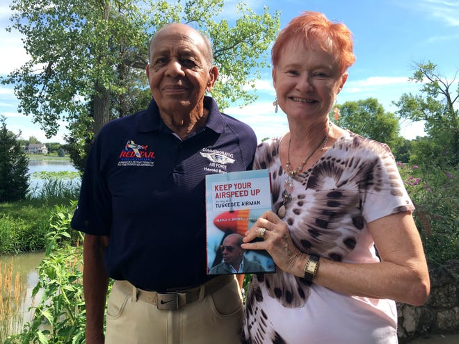 "Marsha Bordner holds up a copy of ""Keep Your Airspeed Up,"" a book she co-authored with her husband, Harold Brown, about his life and experiences during World War II as a Tuskegee Airman. The Commemorative Air Force (CAF) Red Tail Squadron announced that Brown will be inducted into the Minnesota Aviation Hall of Fame. Brown and Bordner together also received recognition as CAF Writers of the Year for their book."