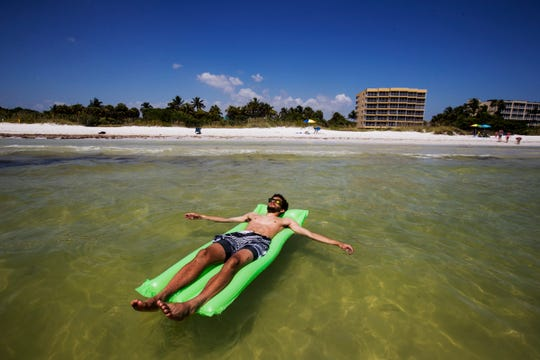 Dre Scott relaxes in the Gulf of Mexico at  Bowditch Point Park on Fort Myers Beach on Monday, June 25, 2019. He was trying to stay cool as record temperatures could drive the heat index to 109 degrees.